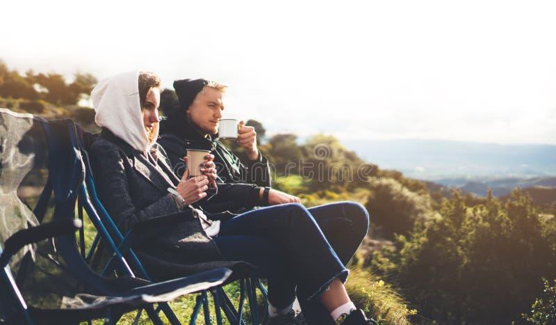 Les couples d'amour se reposent dans les chaises campantes sur la montagne de fusée du soleil, voyageurs boivent du thé sur la ta images stock