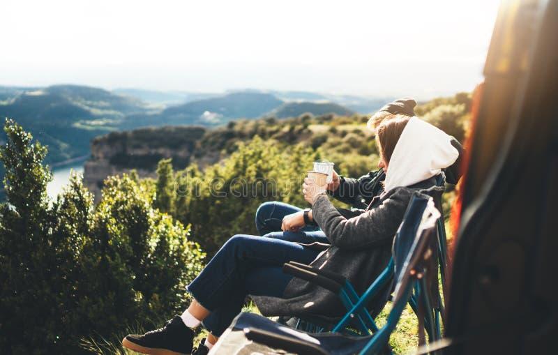 Les couples d'amour se reposent dans les chaises campantes sur la montagne de fusée du soleil, voyageurs boivent du thé sur la ta images libres de droits
