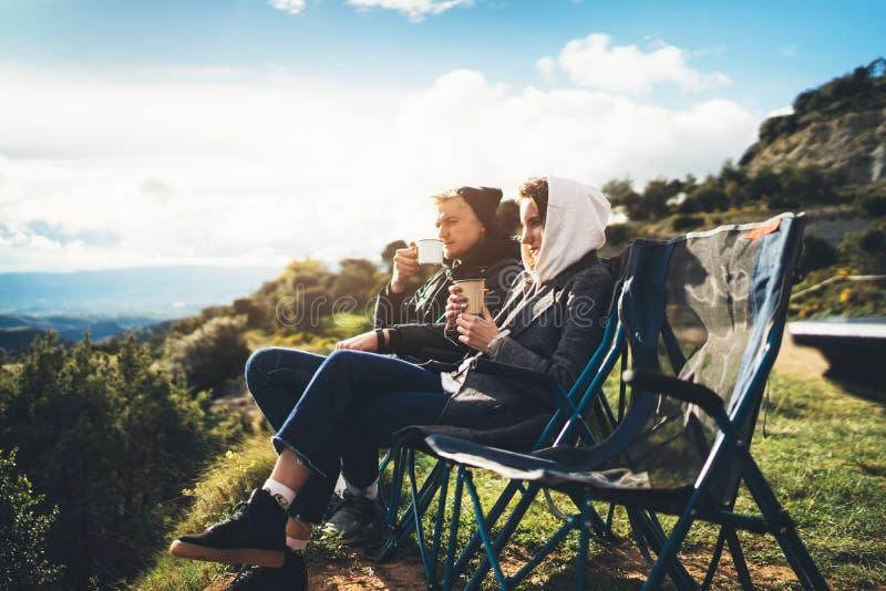 Les couples d'amour se reposent dans les chaises campantes sur la montagne de fusée du soleil, voyageurs boivent du thé sur la ta photographie stock libre de droits
