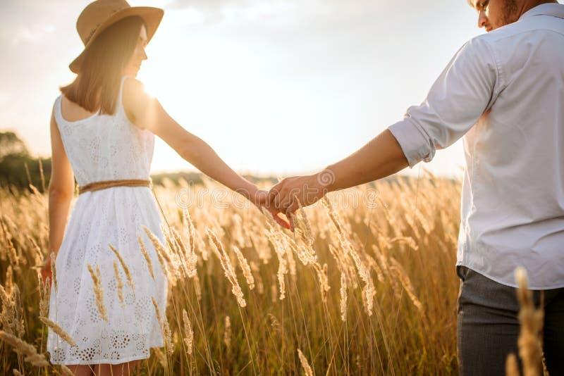 Les couples d'amour tiennent des mains dans un domaine de seigle sur le coucher du soleil photos stock