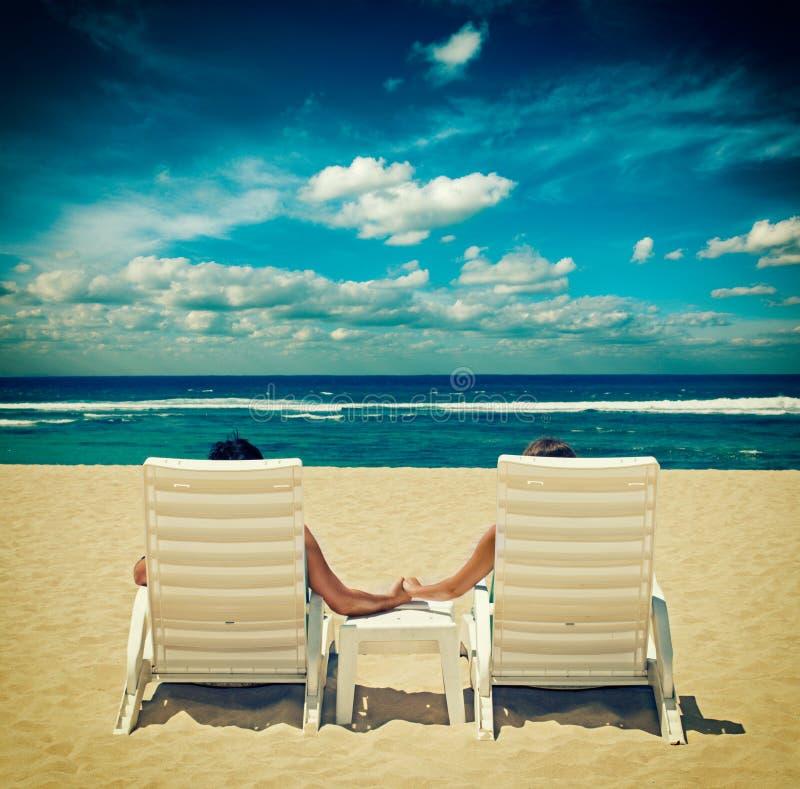 Les couples dans des chaises de plage tenant des mains s'approchent de l'océan photographie stock