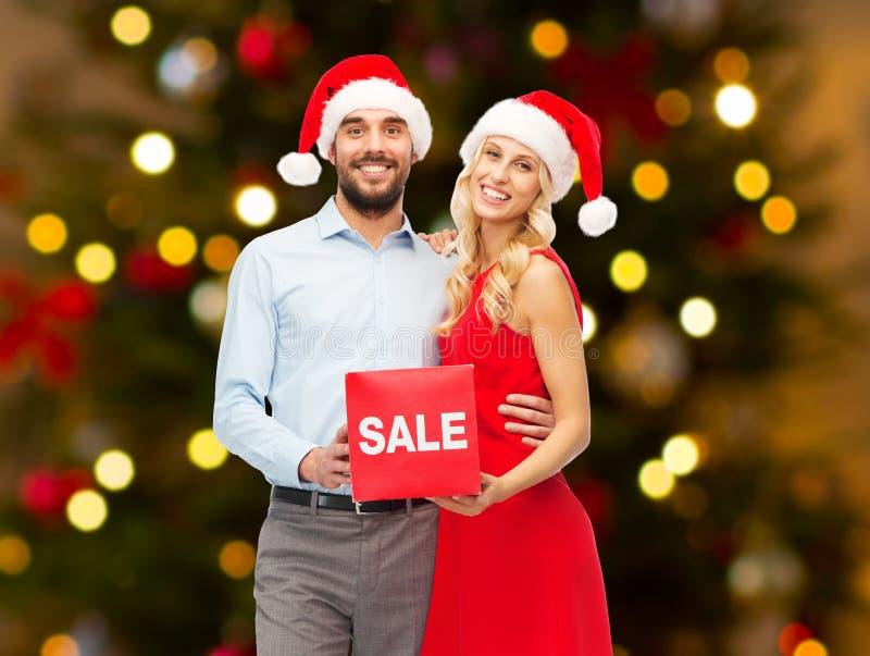 Les couples dans des chapeaux de Santa avec la vente se connectent Noël photographie stock libre de droits