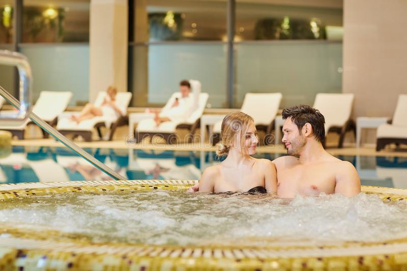 Les couples dans des maillots de bain dans la station thermale de repos de piscine centrent photo libre de droits