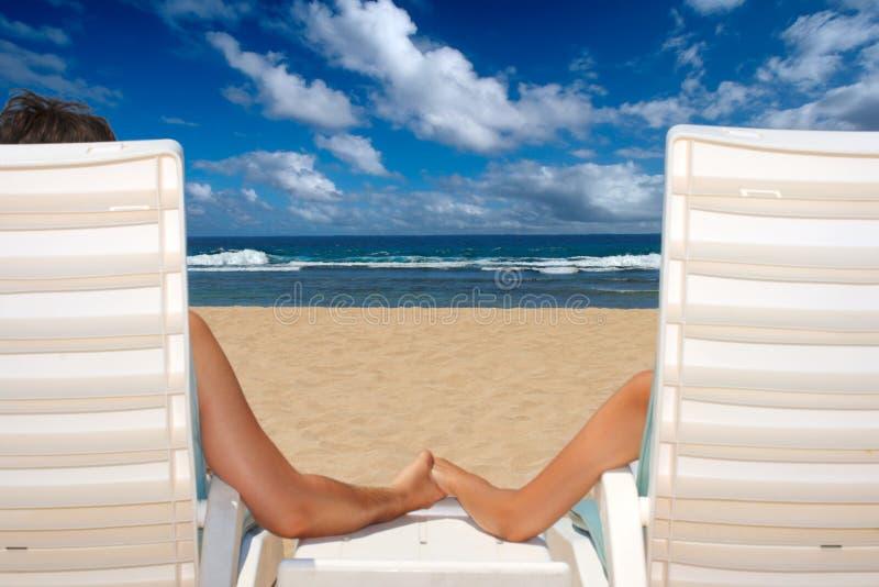 Les couples dans des présidences de plage retenant des mains s'approchent de l'océan photos stock
