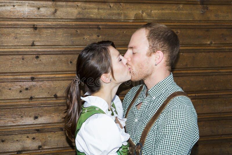 Les couples dans des vêtements bavarois traditionnels embrassent image libre de droits