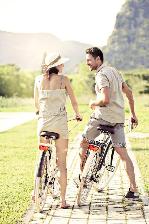 Les couples dans l'amour ont un tour avec des bicyclettes dans la nature photographie stock libre de droits