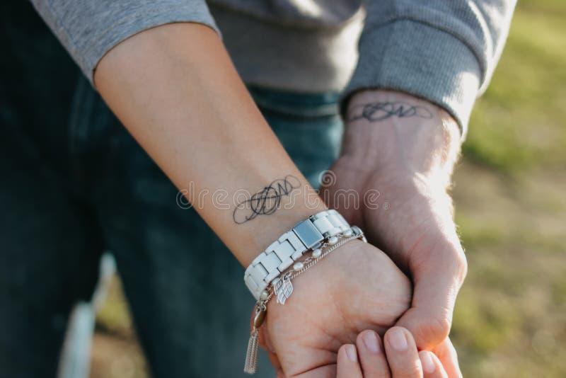 Les couples dans l'amour se tenant de pair Initiales appareillées de tatouage sur les bras images stock