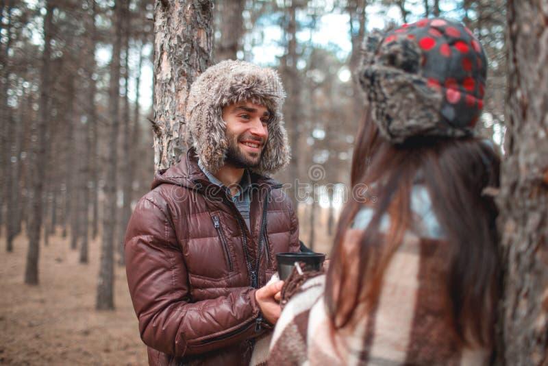 Les couples dans l'amour, sont dans des mains d'une forêt froide et de prise d'automne et regardent l'un l'autre photographie stock libre de droits