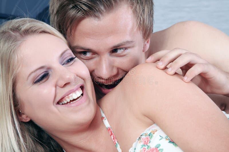 Les couples dans le lit et embrassent le cou photo stock