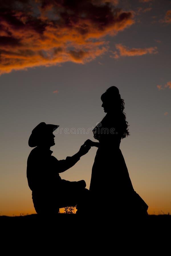 Les couples de cowboy le silhouettent agenouillement images libres de droits