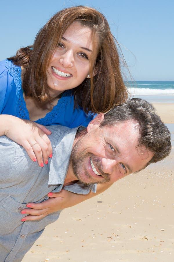 les couples de femme et d'homme de ferroutage dans l'amour sur la plage de sable vacation images libres de droits
