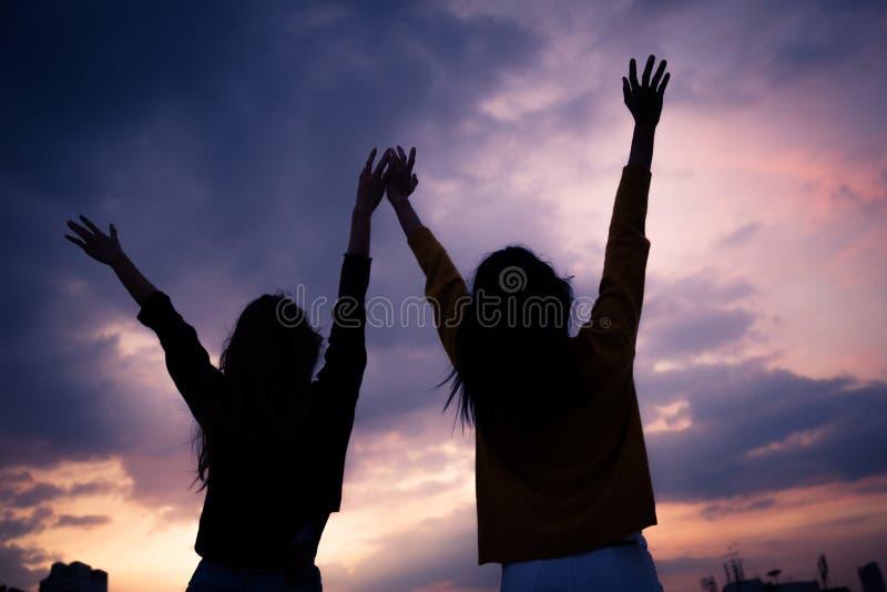 Les couples de la jeune position asiatique de femme ouvrent ses bras au suset photos stock