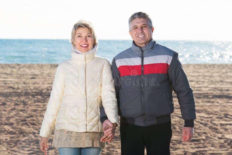 les couples de plage mûrissent la marche photographie stock