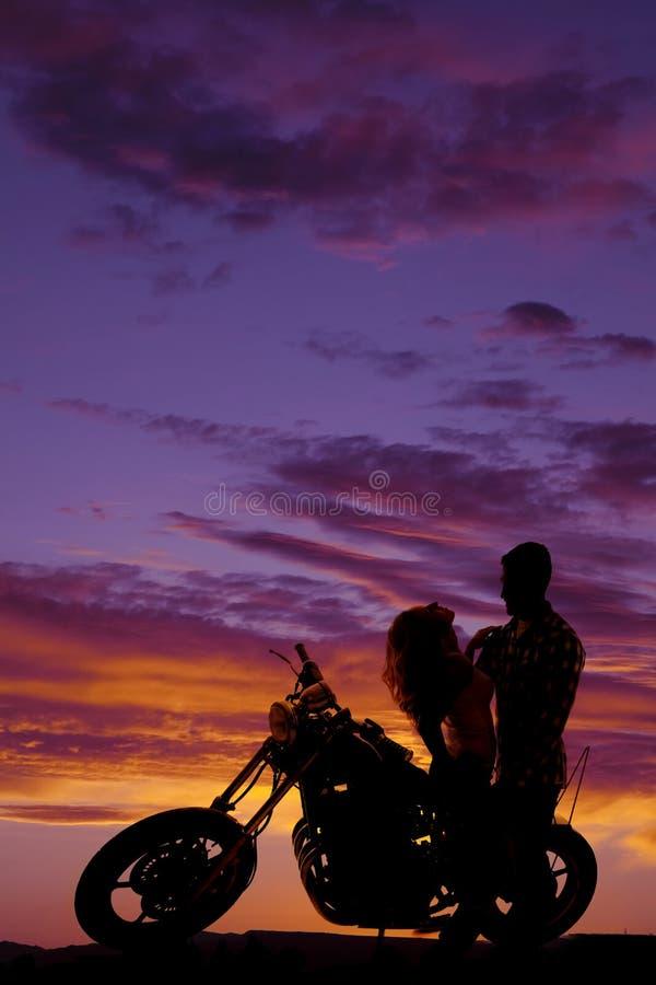 Les couples de silhouette ensemble sur la moto sa se penchent de retour image stock