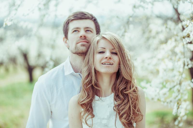 Les couples de sourire heureux détendant dans le pommier de floraison font du jardinage Homme recherchant Tir horizontal de portr photographie stock