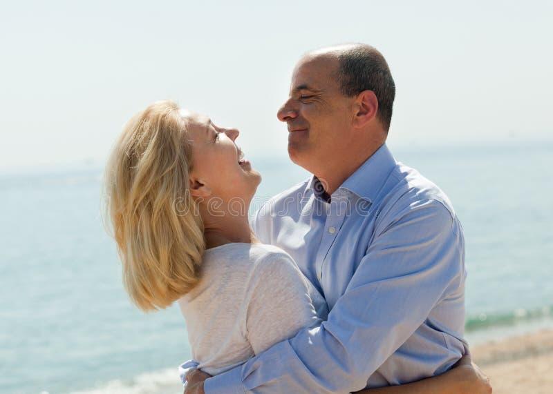 Les couples de touristes d'Eldelry en mer échouent sur le sourire de vacances photo libre de droits