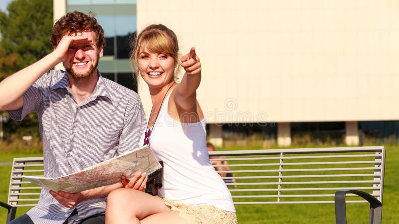 Les couples de touristes dans la ville ont lu la carte photo stock