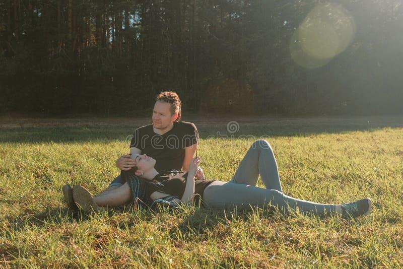 Les couples des amants détendent en parc se trouvent sur l'herbe et la causerie photo stock