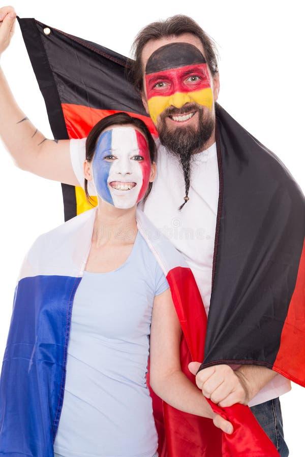 Les couples des fans françaises et allemandes sourient, d'isolement sur le blanc photo stock