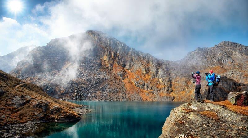 Les couples des randonneurs prennent des photos du lac de montagne contre photo libre de droits