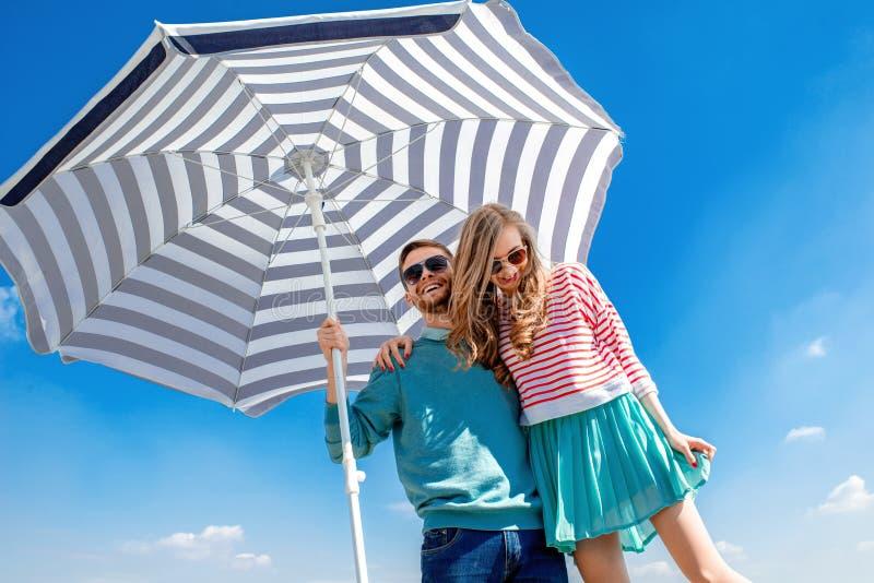 Les couples drôles et jeunes ont l'amusement avec le parapluie de plage sur le toit photographie stock