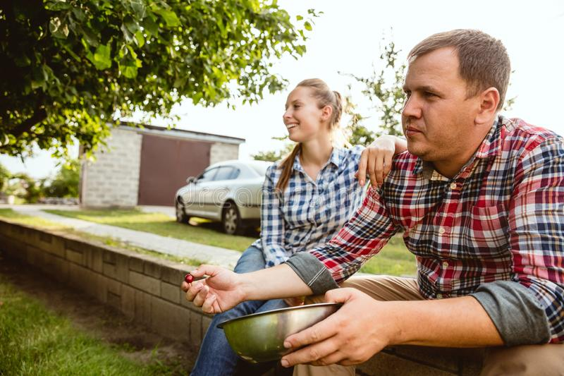 Les couples du jeune et heureux agriculteur à leur jardin dans le jour ensoleillé images stock