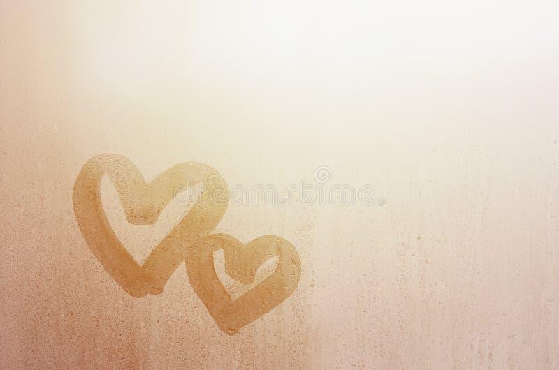Les couples du résumé ont brouillé le symbole de coeur d'amour dessiné à la main sur le verre de fenêtre humide avec le fond de l photo libre de droits