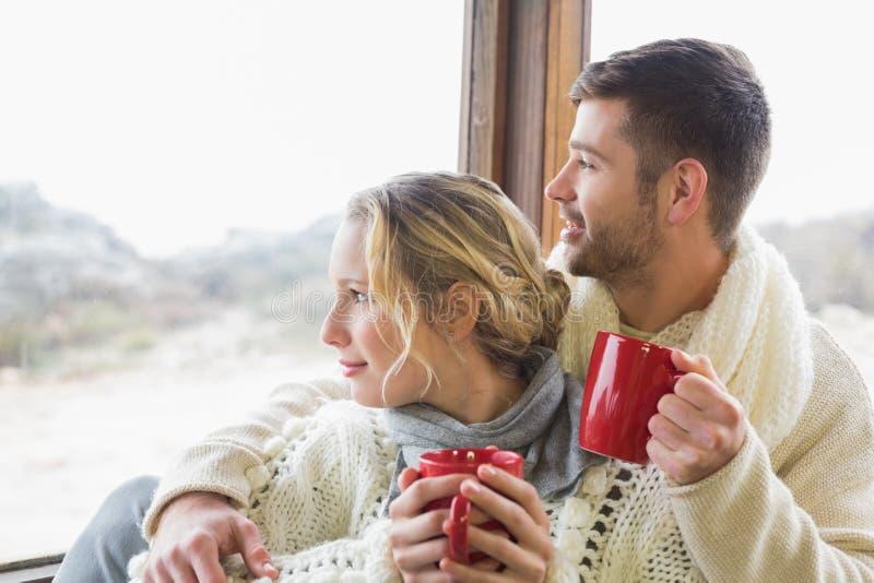 Les couples en hiver portent avec des tasses regardant par la fenêtre photos stock