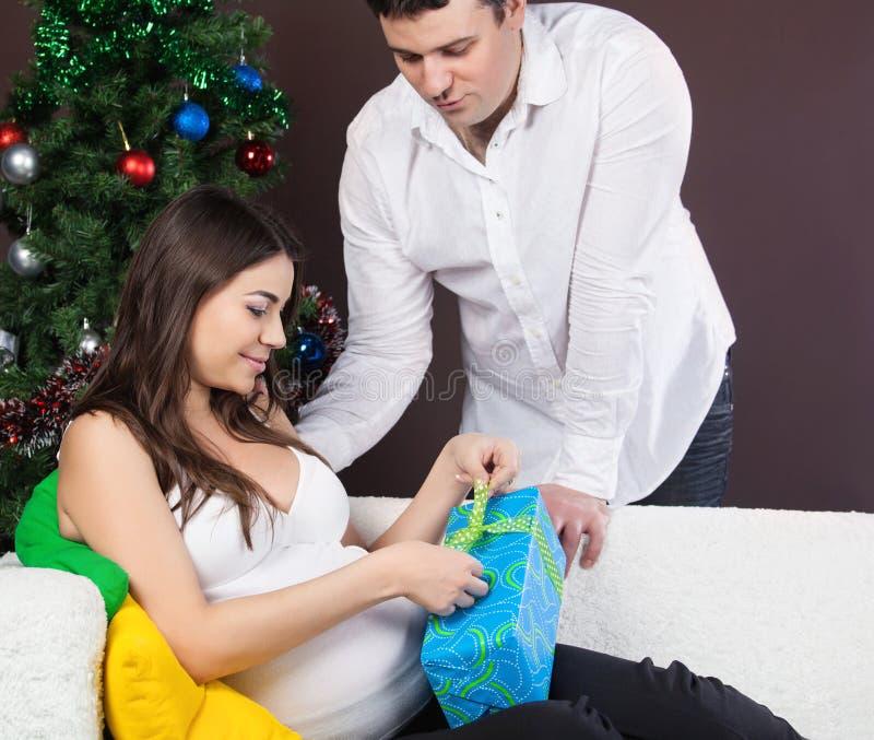 Les Couples Enceintes Heureux S Approchent De L Arbre De Noël Images stock