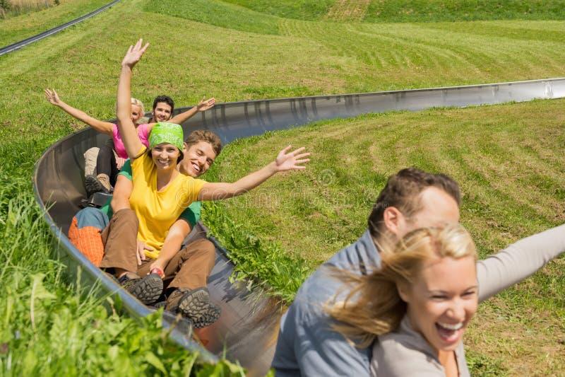 Les couples enthousiastes appréciant le caboteur alpin Luge images libres de droits