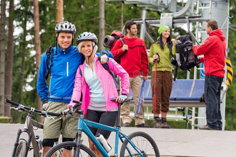 Couples et randonneurs de vélos de montagne après ascenseur de chaise photo stock