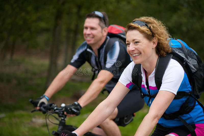 Les couples gais appréciant un vélo montent en nature photo stock