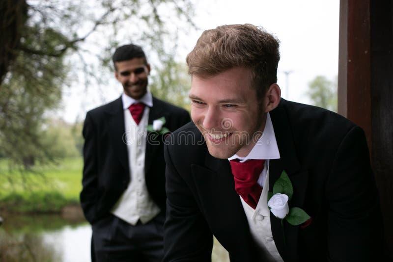 Les couples gais des mariés posent pour des photographies par un lac leur jour du mariage photos stock