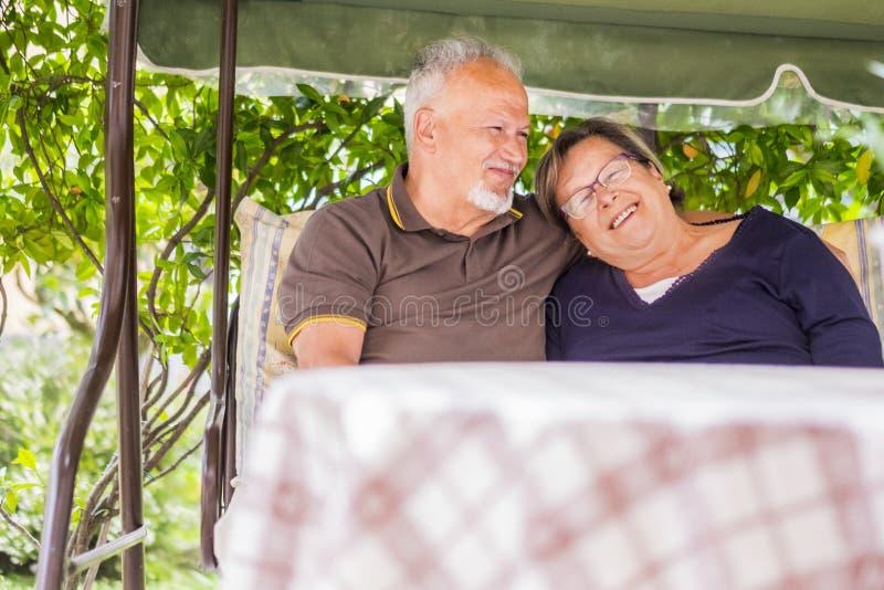 Les couples gentils de belles 70 années supérieures caucasiennes reposent extérieur à la maison ayant l'amusement avec des sourir photographie stock