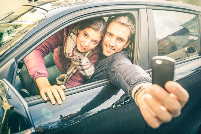 Les couples heureux à la voiture louent la représentation que principaux électroniques préparent pour disparaître images stock