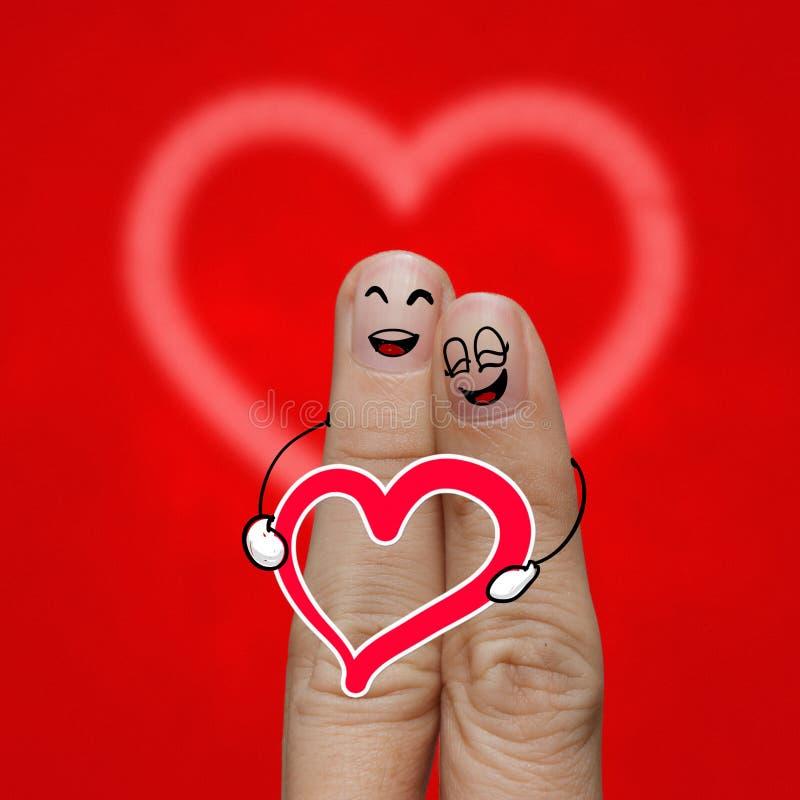 Les couples heureux de doigt dans l'amour avec le smiley peint photo libre de droits