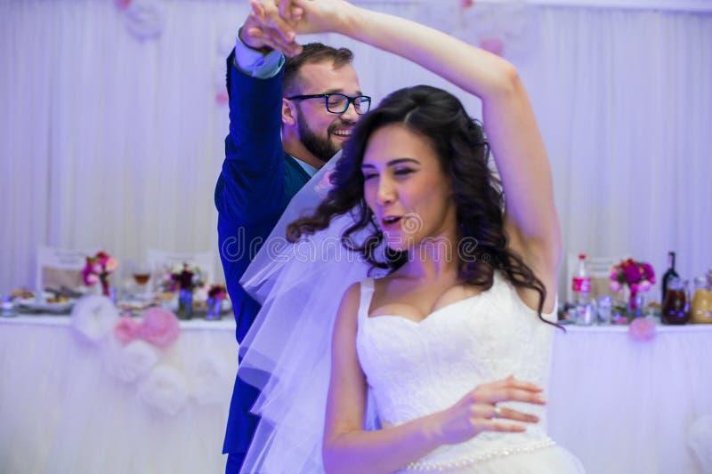 Les couples heureux de nouveaux mariés ayant l'amusement pendant leur première danse à les épousent photos libres de droits