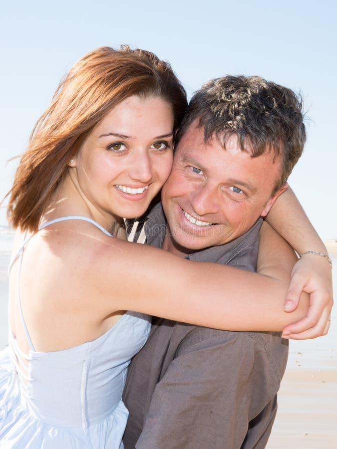 les couples heureux de sourire dans l'amour jouent le jour de vacances d'été de plage de sable photo libre de droits
