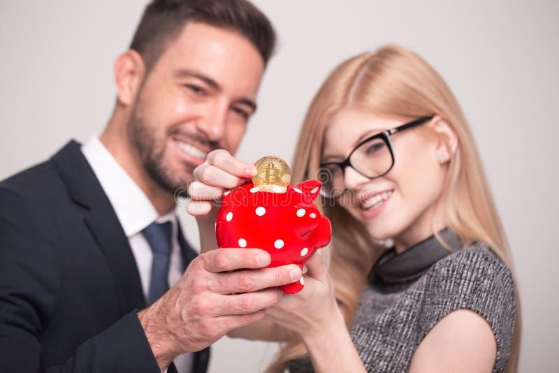 Les couples heureux laissent tomber le bitcoin dans la tirelire photos libres de droits