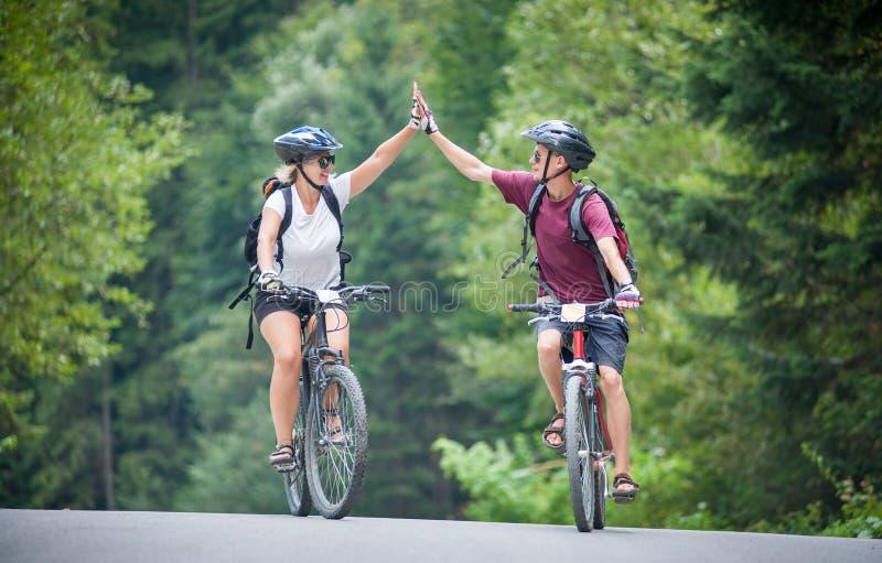 Les couples heureux montent sur une route goudronnée de montagne sur des vélos image libre de droits