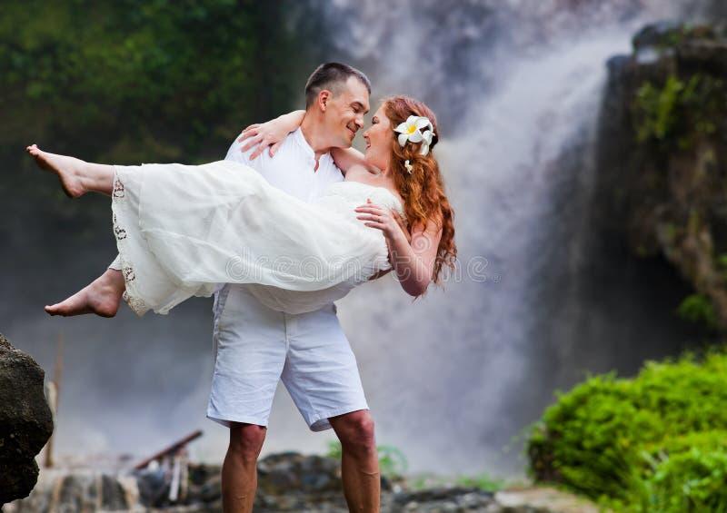 Les couples heureux s'approchent de la cascade photos stock