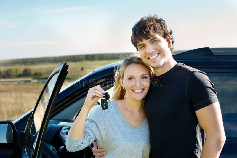Les couples heureux s'approchent du véhicule neuf photos libres de droits