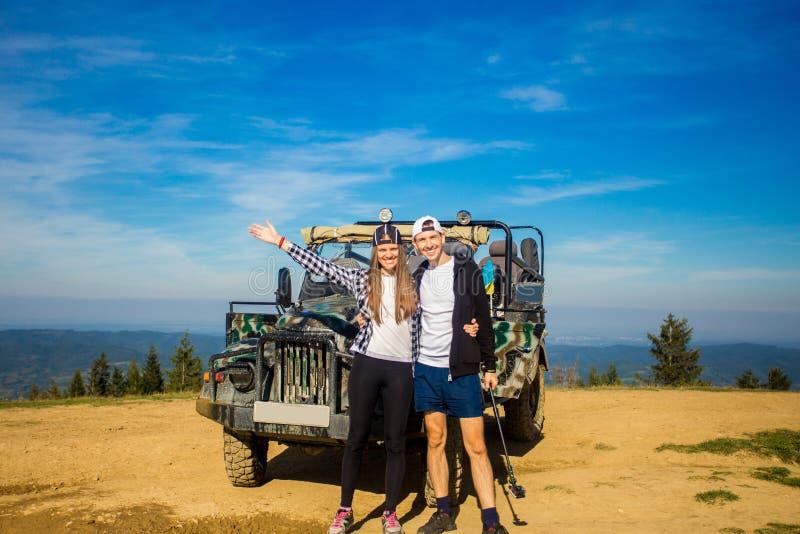 Les couples heureux voyagent en voiture sur le dessus de montagnes photographie stock libre de droits