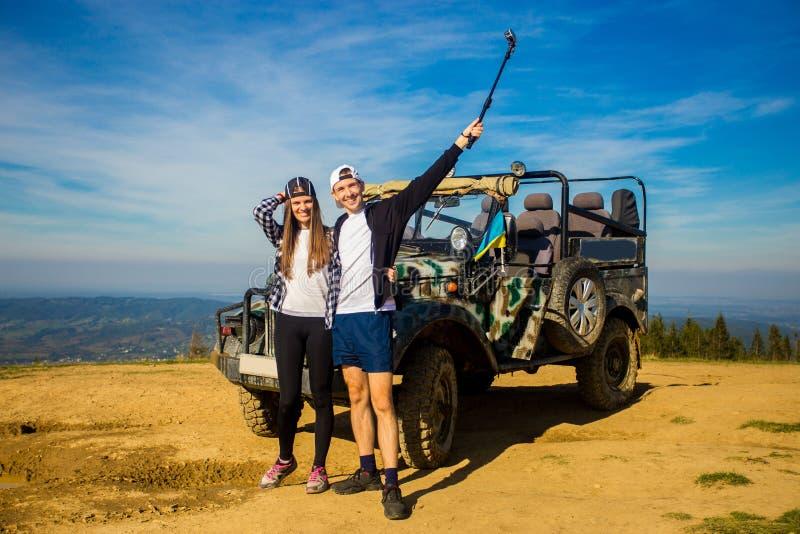 Les couples heureux voyagent en voiture sur le dessus de montagnes photo libre de droits