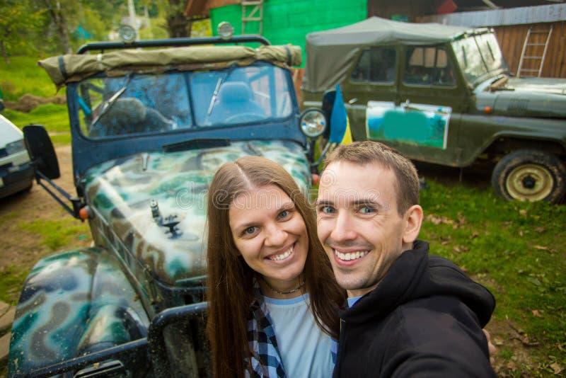 Les couples heureux voyagent en voiture sur le dessus de montagnes image libre de droits