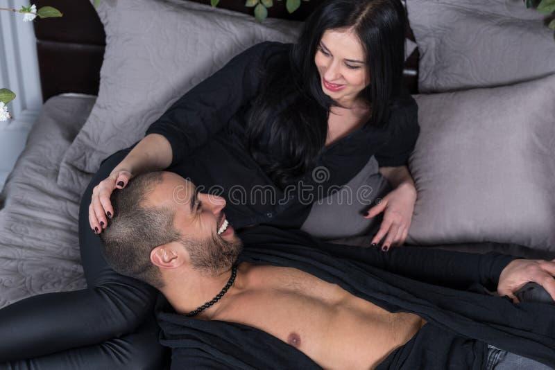 Les couples internationaux attrayants dans des vêtements noirs regardent chaque ot images stock