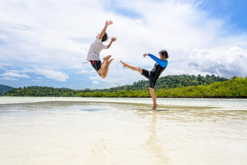 Les couples jouent l'exposition de femme d'amusement donnant un coup de pied un homme sur la plage photo libre de droits