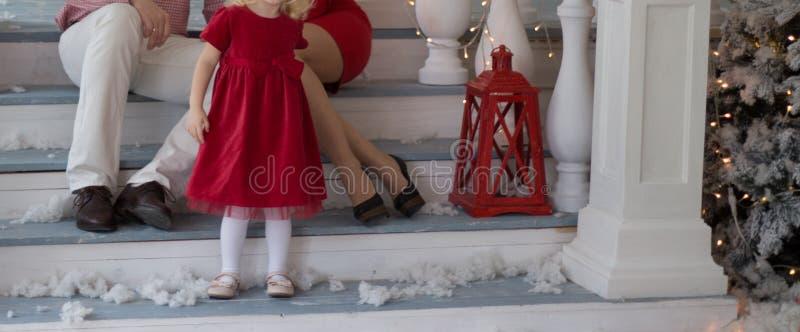 Les couples, le papa et la maman heureux se reposent sur les escaliers de la véranda, maison décorée, Noël à côté des jeux d'enfa photos libres de droits