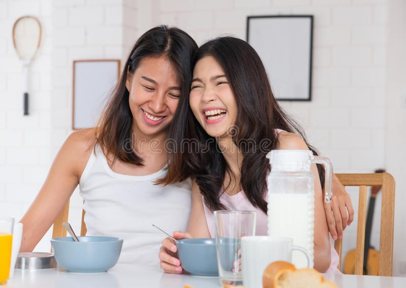 Les couples lesbiens asiatiques heureux de femme prennent le petit déjeuner à la maison dans le matin avec l'amour et l'offre Con photo libre de droits