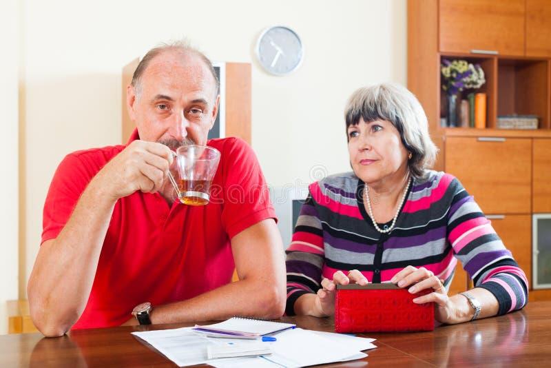 Les couples mûrs n'ont pas eu l'argent sur vos remboursements de prêt images libres de droits